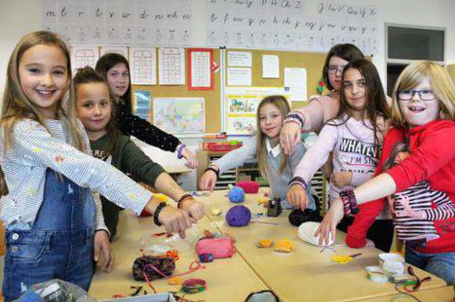 Kinder präsentieren ihre Armbänder