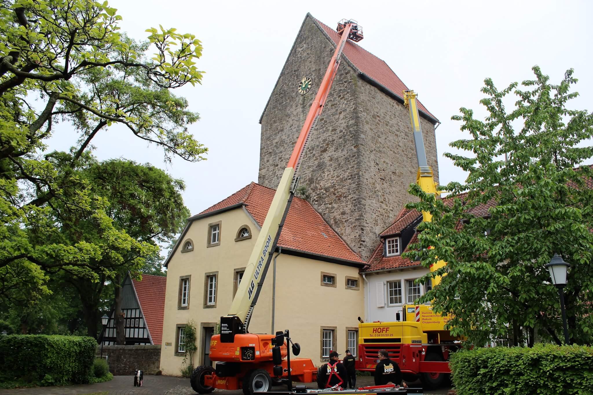 Ein Kranwagen steht mit ausgefahrenem Leiterwagen vor dem Turm der Burg Wittlage