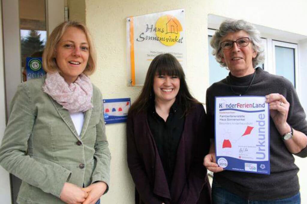 Gruppenbild von drei Frauen vor dem Haus Sonnenwinkel mit einer KinderFerienLand Urkunde