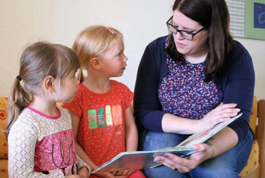 Eine Erzieherin liest zwei Kindern aus einem Buch vor
