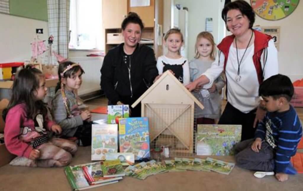 Zwei Erzieherinnen und fünf Kinder präsentieren eine Entdeckerkiste mit Büchern und einem Bienenhotel