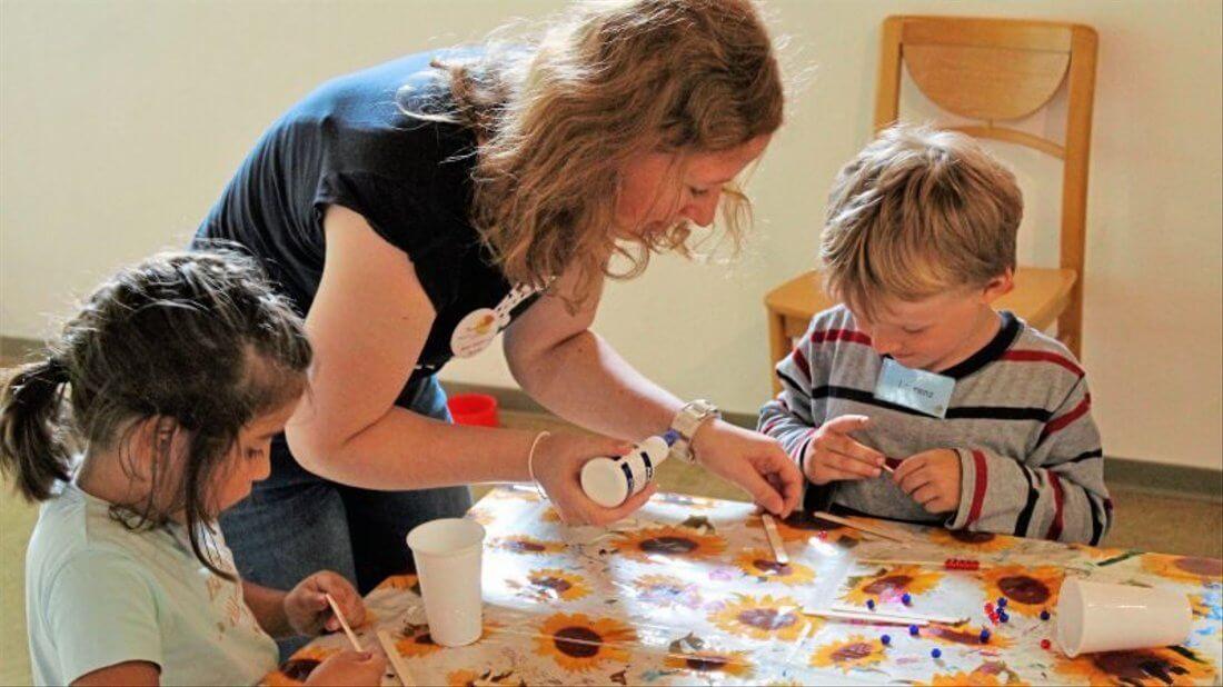 Eine Erzieherin hilft zwei Kindern beim Basteln