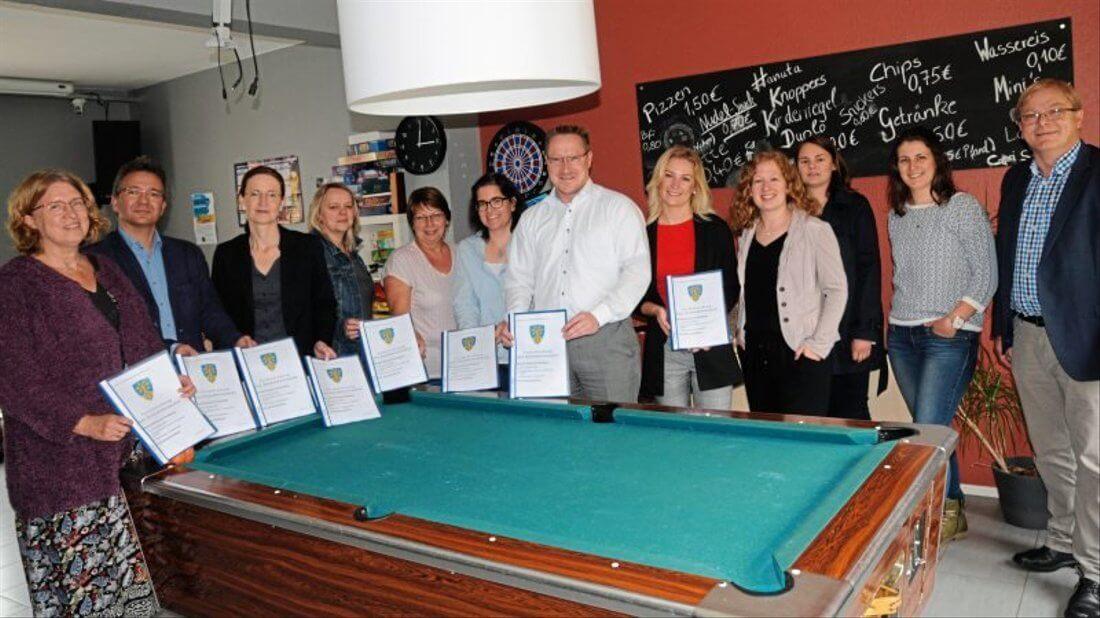 Gruppenbild der Lenkungsgruppe mit Urkunden in einem Billiardraum