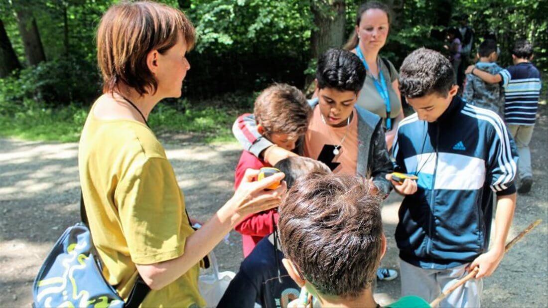 Eine Betreuerin und vier Kinder beim Geocaching in der Natur