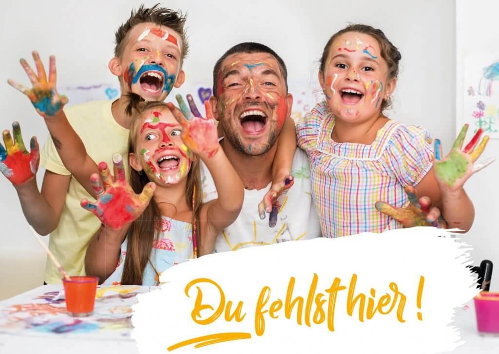 Erzieher und drei Kinder halten freudestrahlend ihre bemalten Hände in die Höhe. Alle haben auch Farbe im Gesicht.