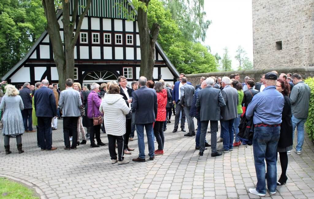 Menschen stehen versammelt vor dem Heuerhaus