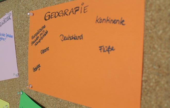 Orangenes Plakat mit Thema Geografie auf Korkwand