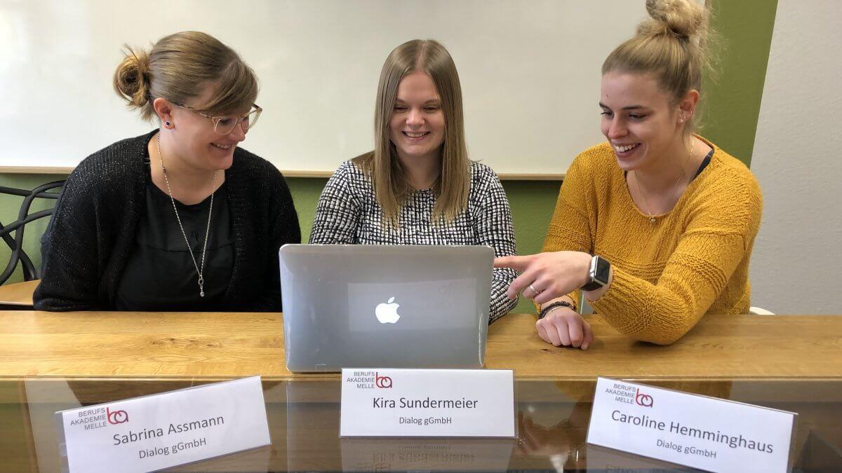 Drei Frauen vom Dialog sitzen am Laptop