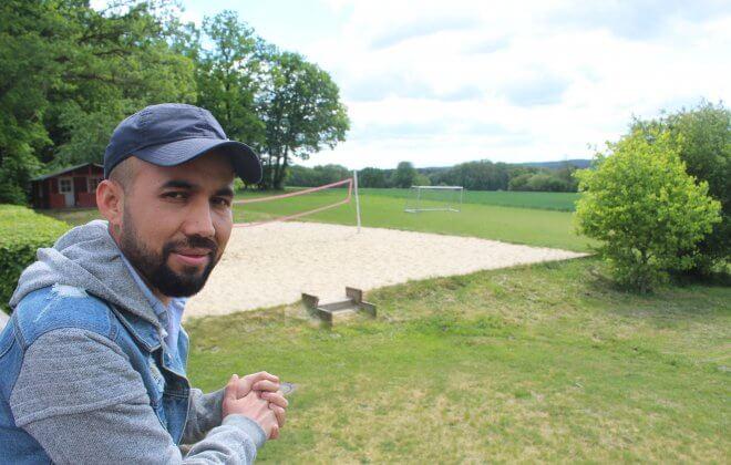 Junger Mann mit Cap steht vor einem Volleyballfeld und schaut in die Kamera