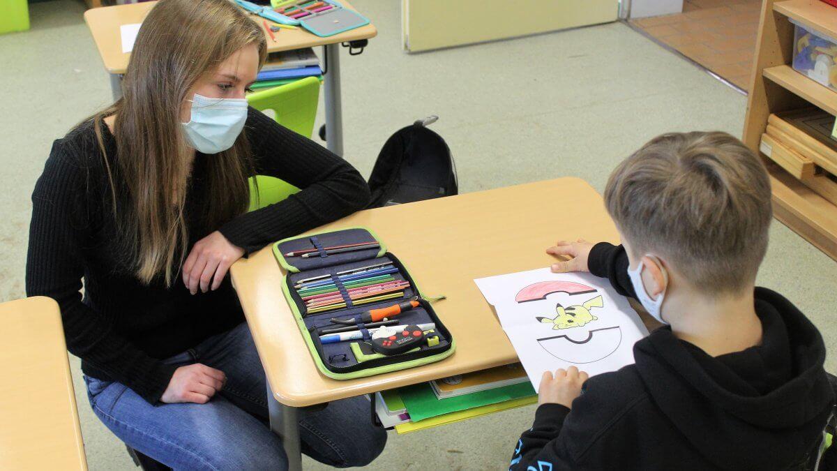 Junge Praktikantin schaut sich das Bild eines Schülers an