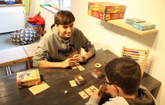 Zwei Jungen spielen ein Kartenspiel am TIsch