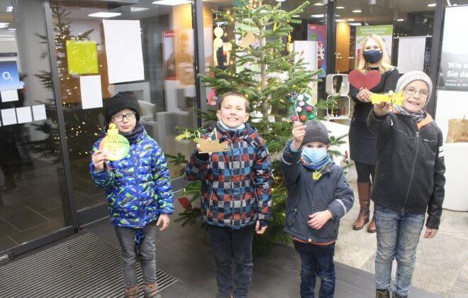 Vier Kinder stehen vor einem Tannenbaum