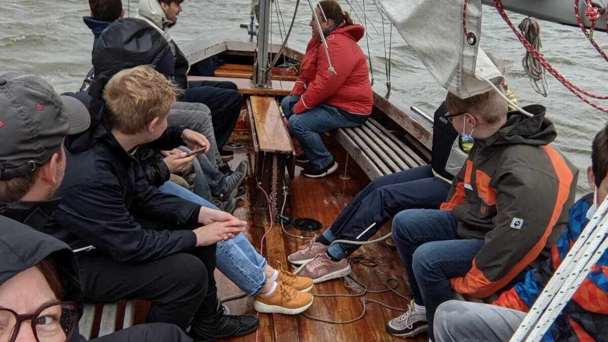 Kinder und Erwachsene sitzen in einem Segelboot