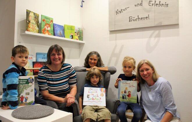 Kinder und Betreuer des Natur- und Erlebniskindergartens zeigen Bücher aus ihrer Bücherei