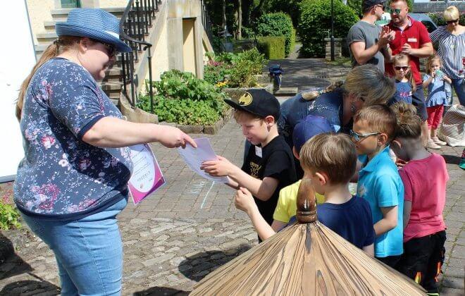 Beutreuerin verteilt Zettel an die künftigen Grundschulkinder