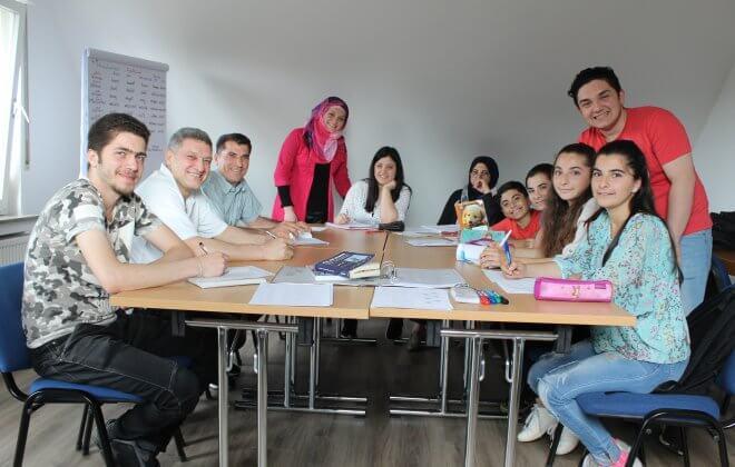 Gruppenfoto von 11 geflüchteten Menschen bei einem Sprachkurs