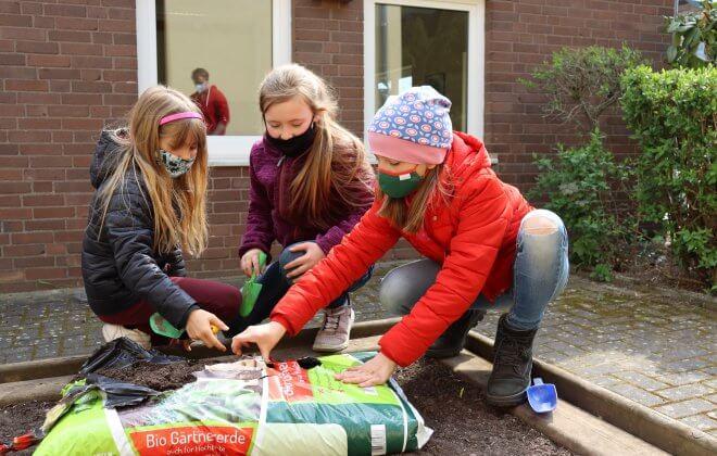 Schüler öffnen einen Sack Gärtner-Erde